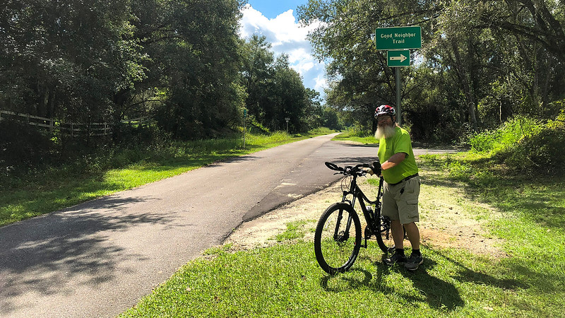 John with bike under Good Neighbor Trail sign