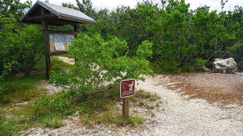 Sign with fishing symbol and rocky path past kiosk in mangroves