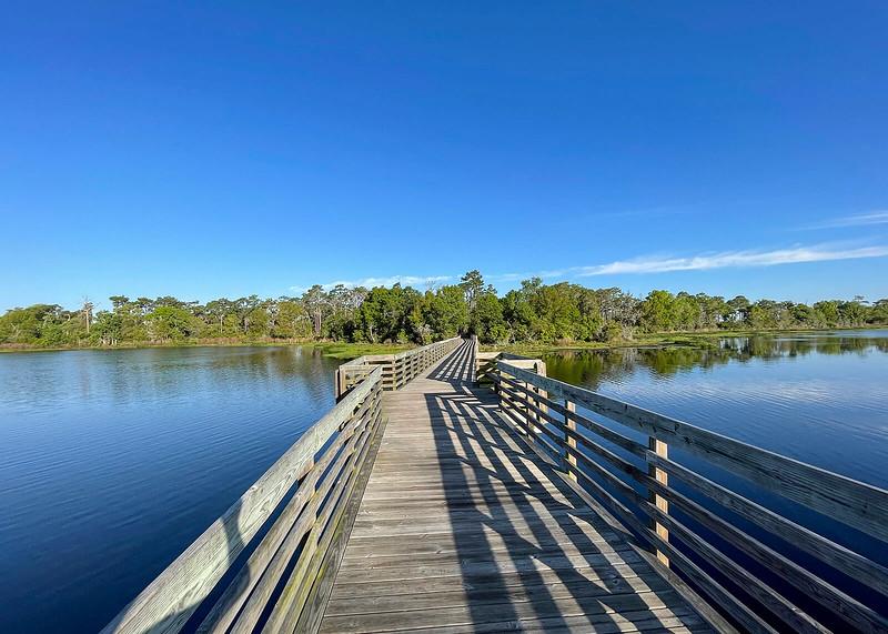 Long boardwalk across a blue lake