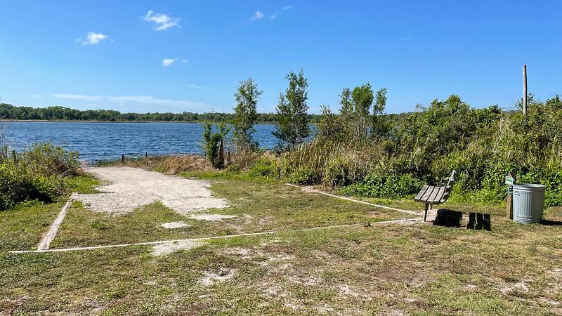 Bench next to sandy area at lake