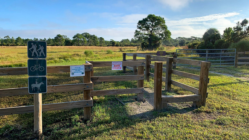 Gate and stile with signs and baffle at trailhead