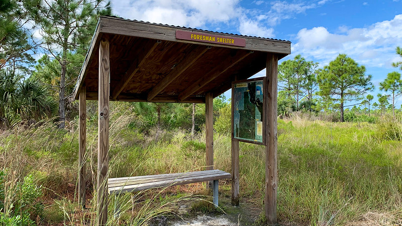 Shelter with sign and protected bench and map