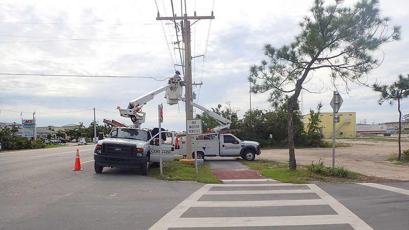 Utility trucks parked on the bike path