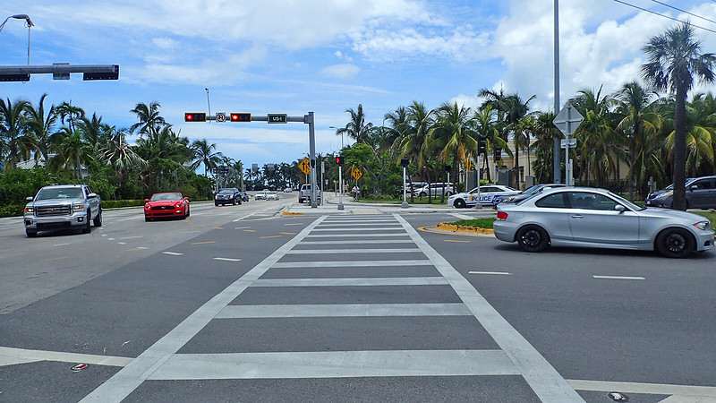 Lots of traffic at a crosswalk with traffic light