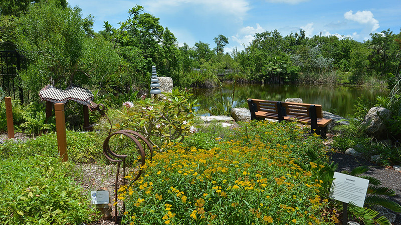 Bench overlooking pond with sculpture in flower beds