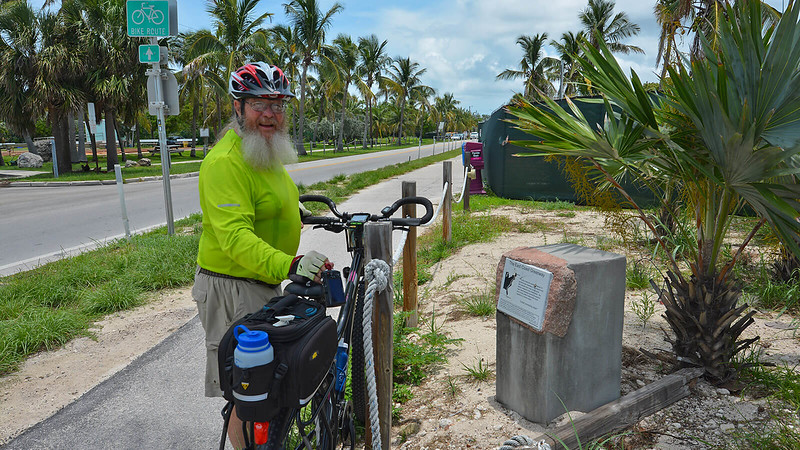 John standing with bike at trail marker