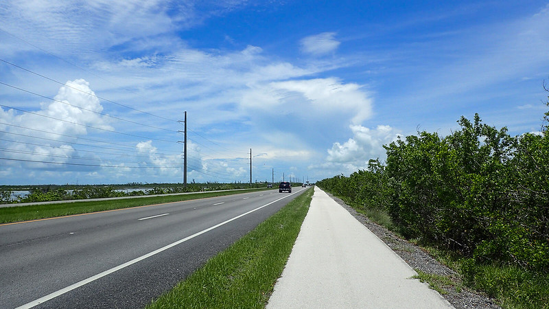 Bike path adjoining highway with water on west horizon