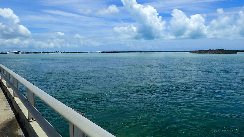 Looking over metal bridge railing to teal water and islands