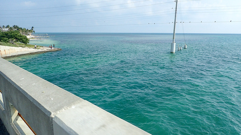 Bridge nears shoreline with teal water and white coral rock beach