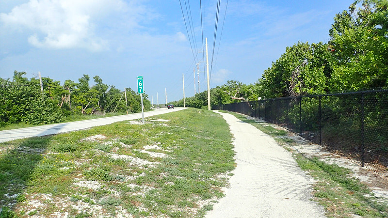 Bike path adjoins black chain link fence