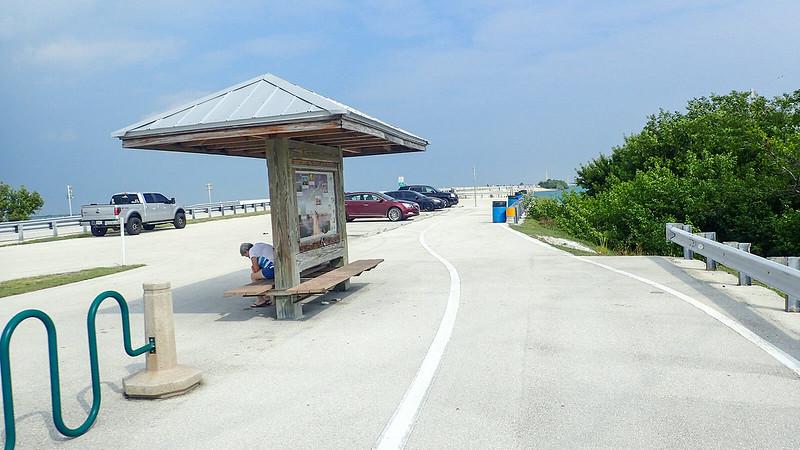 Bike path past kiosk adjoined by bike rack