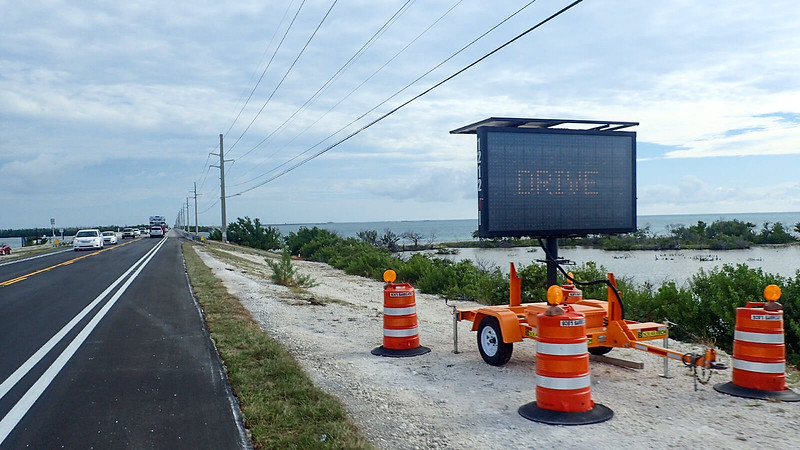 Digital sign adjoining bike lane along island with mangroves beyond