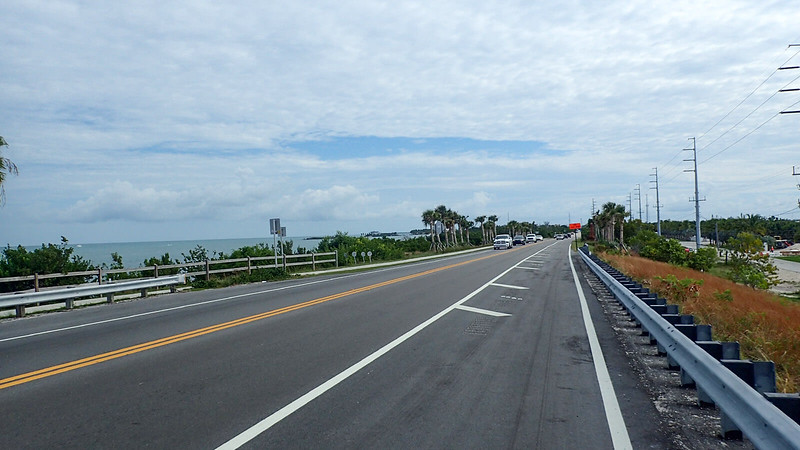 Highway with guardrail on right and bike path opposite side