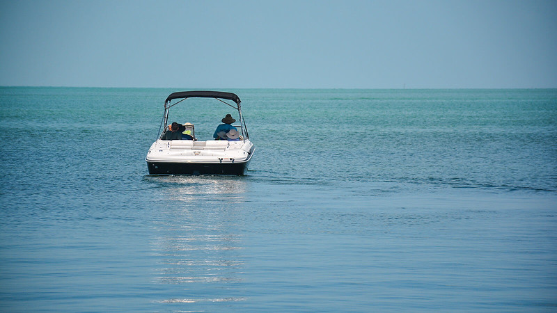 Boat pointed away from shore in aquamarine waters