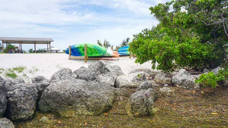 Rocks in foreground with white sand, kayaks, and picnic pavilion beyond
