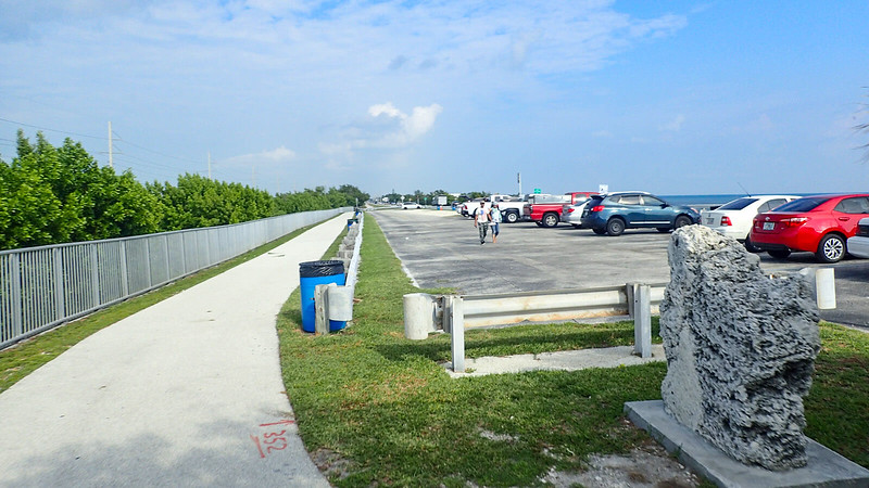 Cars parked under blue skies with bike path on left side of parking area