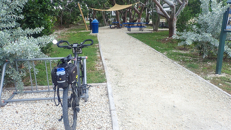 Bike parked in bike rack in front of forested area with picnic tables
