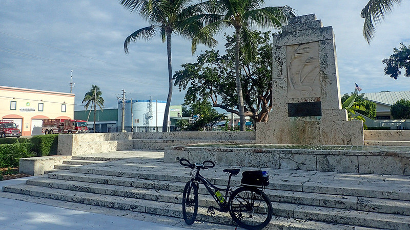 Bike in front of art deco monument with waving palms in stone
