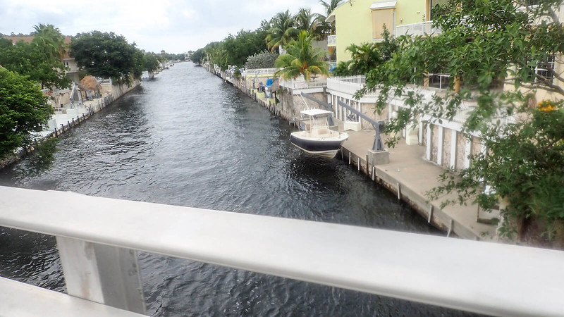 Looking over railing at canal behind residences with a boat at anchor
