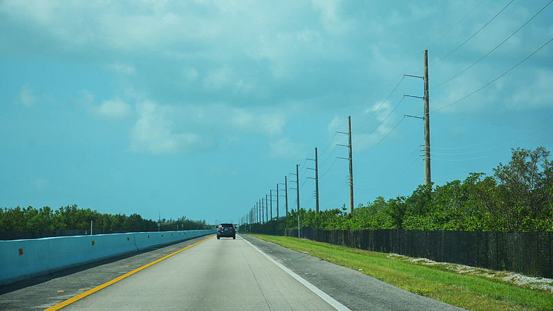 Long road with barriers fences and power lines