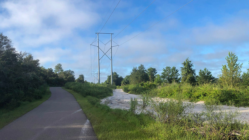 Bike path next to white sand and power lines