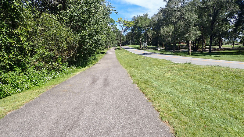 Broad paved path on rolling rural terrain