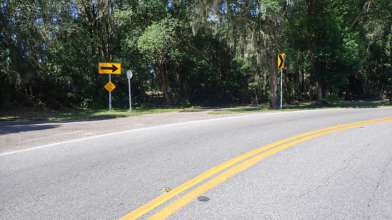 Curve in road with arrow sign and obscured bike path