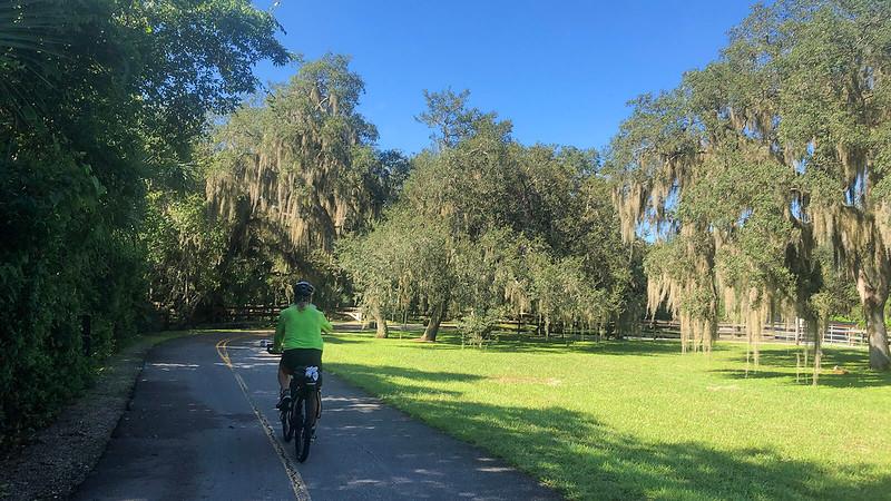John on bike in grassy open area with live oaks