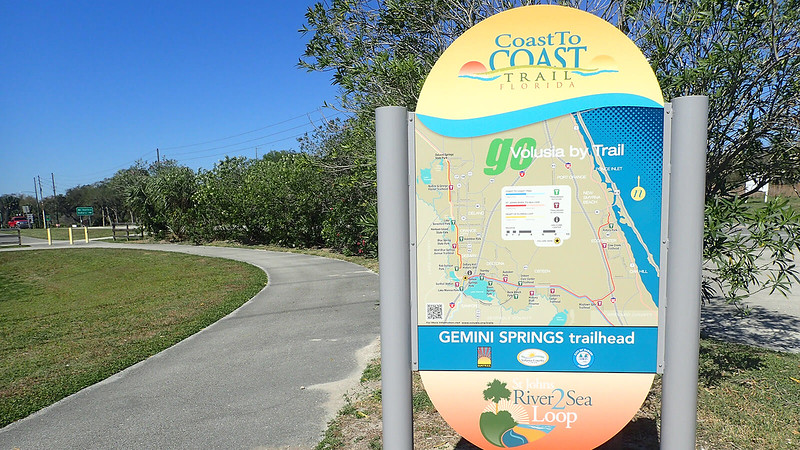 Map signage along bike path near road