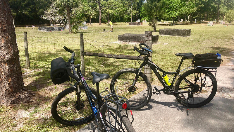Two bikes parked in front of historic cemetery