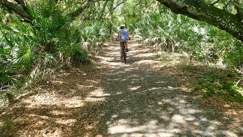 Sandra biking on cinder path in dense palm and oak forest