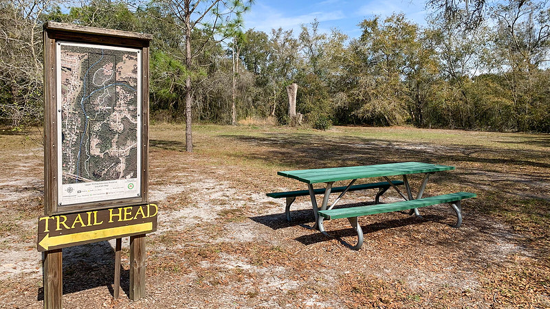 Trailhead sign and map next to picnic bench