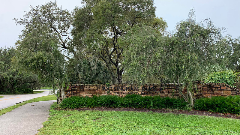 Stone wall with park name under trees