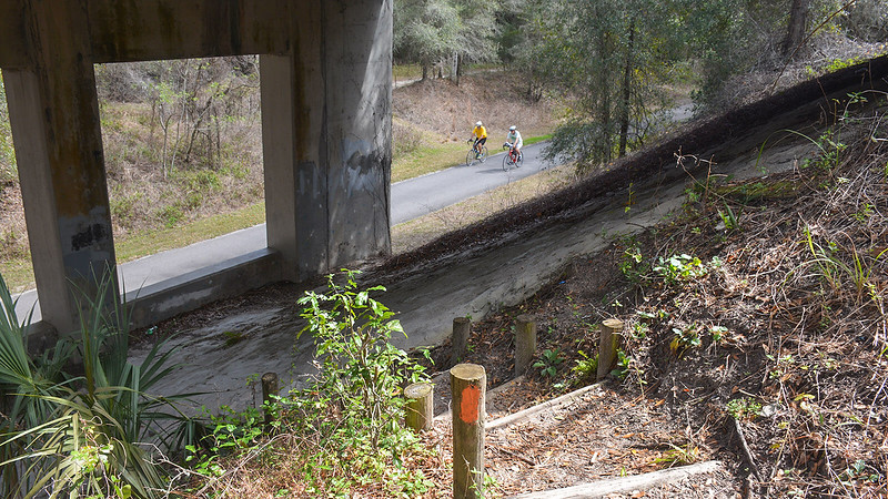 Cyclists passing stairs beneath an underpass