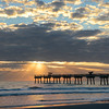 Sun rising over  ocean horizon and pier.