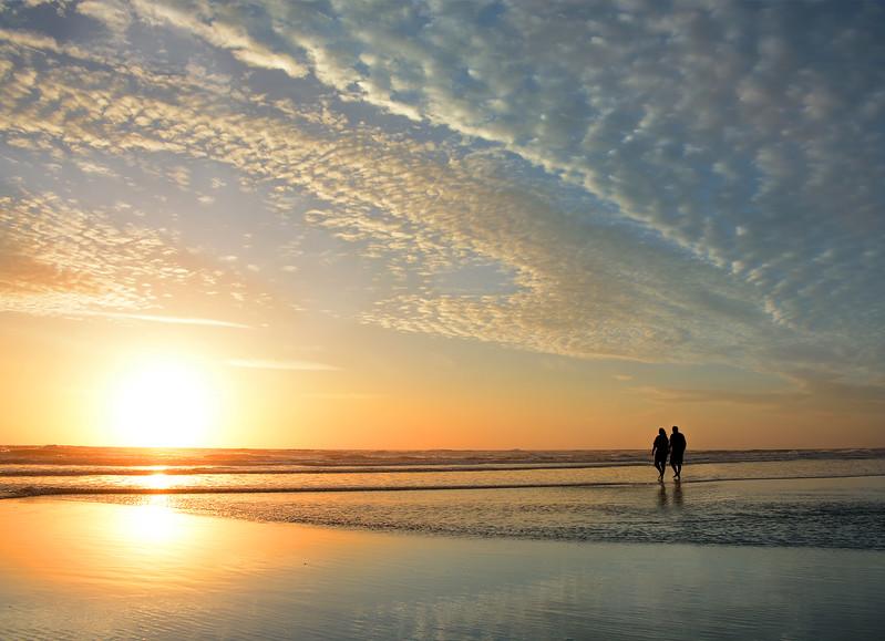 Couple walking on beach at sunrise,