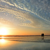 Couple walking on beach at sunrise,