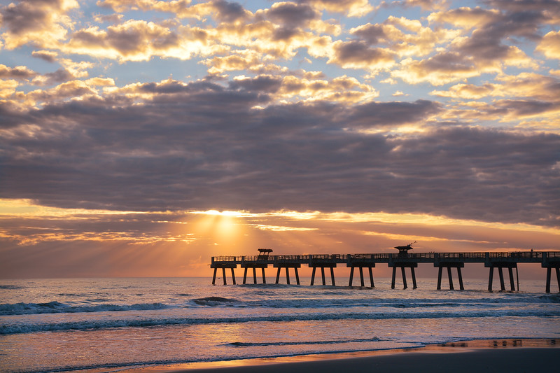 Sunrise over ocean horizon and pier.
