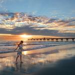 Happy, smiling girl enjoying time on  beautiful beach at sunrise.