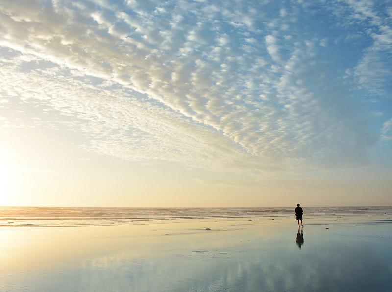 Man walking on beautiful beach at sunrise.