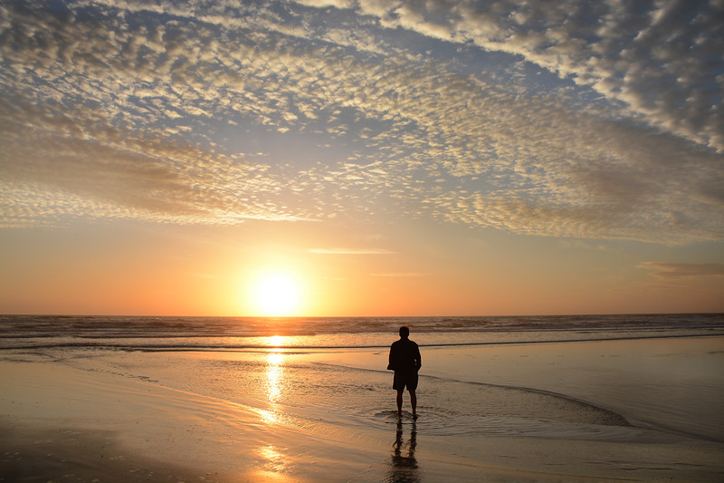 Man walking on beach at sunrise.