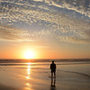 Man walking on beach at sunrise.