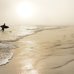 Man  with surfboard on the beautiful foggy beach.