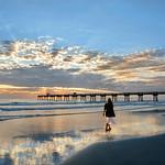 Woman walking on the beautiful beach at sunris