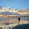 Woman walking on the beautiful beach at sunris