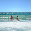 Friends  having fun in big waves in beautiful ocean.