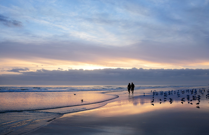 Couple holding hands walking on beautiful beach at sunrise.
