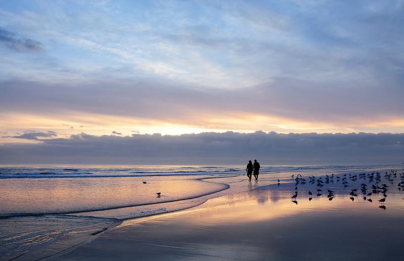 Couple holding hands walking on beautiful beach at sunrise.