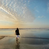 Girl walking on the beach at sunrise.