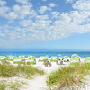 Summer landscape.Sand dunes, blue sky with clouds, and green ocean in the background.  Beach chairs and parasols on beautiful white sand. Gulf of Mexico, Clearwater Beach, Florida, USA.